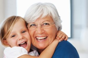 Closeup portrait of senior Caucasian woman hugging cheerful little granddaughter